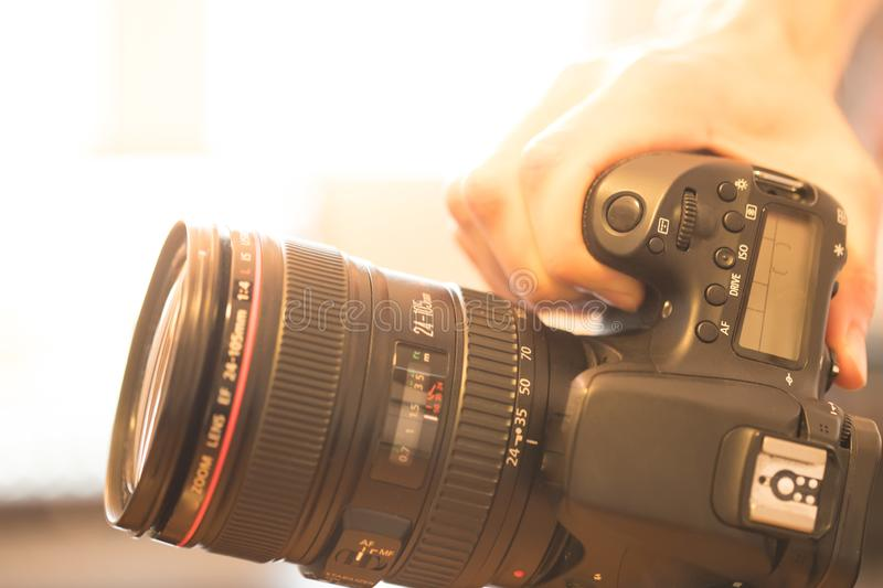 Photographer is holding a professional camera with telephoto lens in his hand, laptop in the blurry background. Photographer holds a reflex camera with telephoto stock images