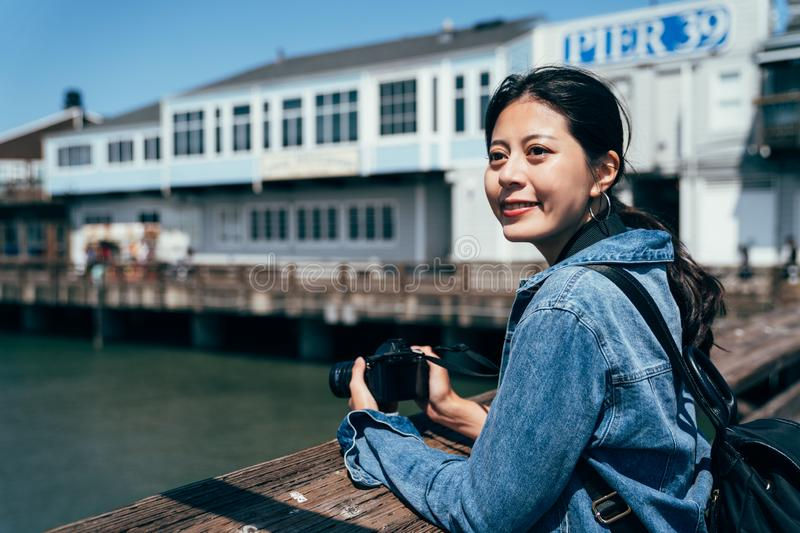 Photographer holding slr camera on port. Young girl tourist visit pier 39 in san francisco. female photographer holding slr camera taking photo on port on sunny stock image