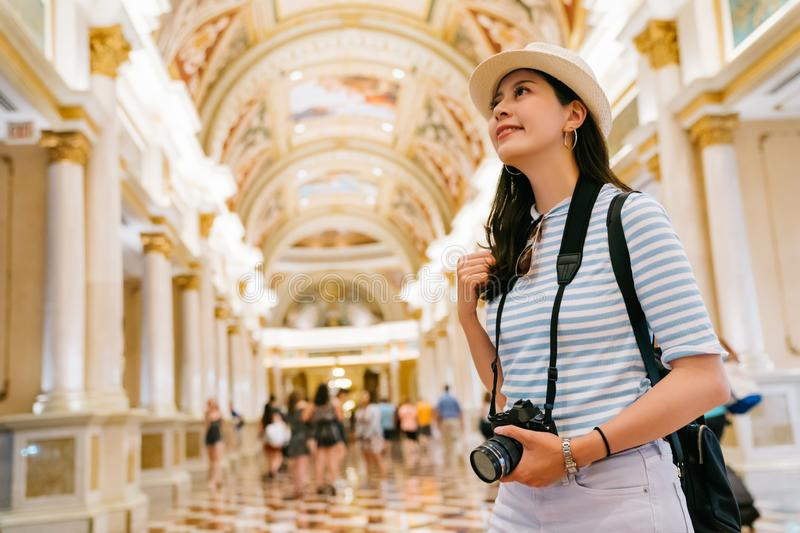 Photographer looking up to the classic ceiling. Elegant photographer standing in the building and looking up to the classic design ceiling. young lady lens man stock photography