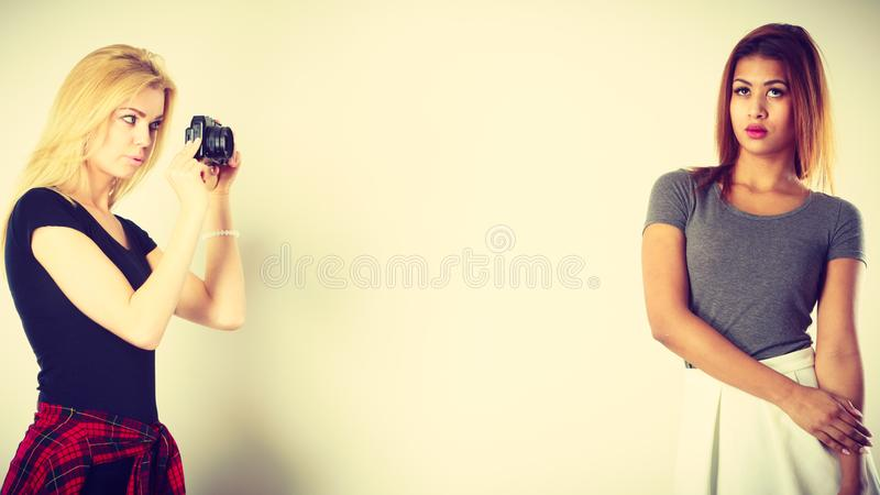 Blonde girl photographing mulatto woman royalty free stock images