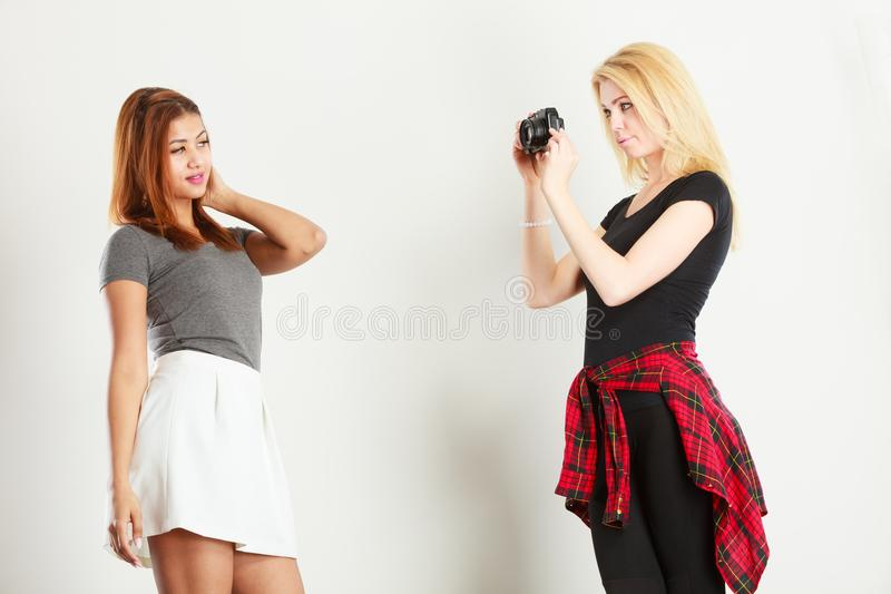 Blonde girl photographing mulatto woman stock image