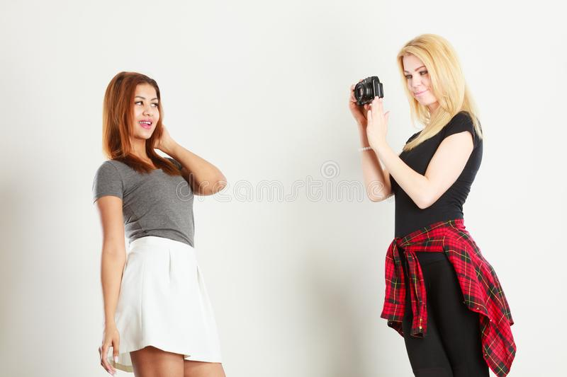 Blonde girl photographing mulatto woman stock photography