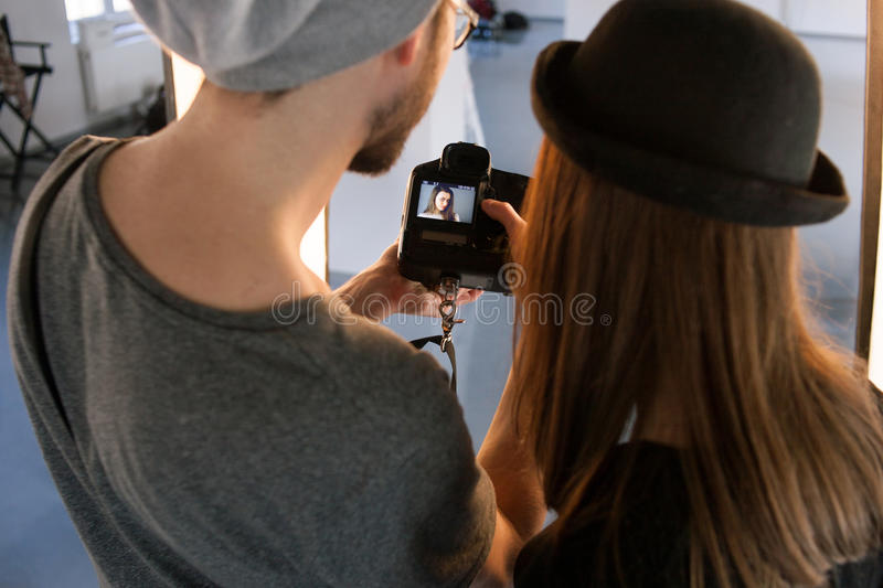Photographer and model watching photos on camera. Top view. Man with camera show pictures to casual women during the studio session. Production of commercials stock images