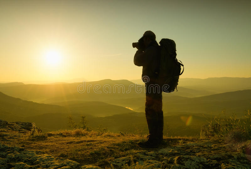 Photographer in mountains. High contrast, warm toned stock photos