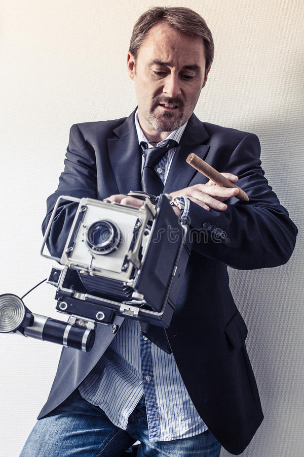 Photographer with old camera looking at his watch stock photo