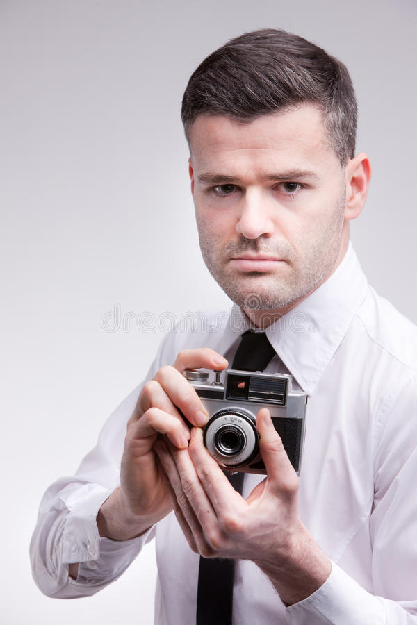 photographer with an oldstyle analogue photocamera shooting photographs with a serious expression stock image