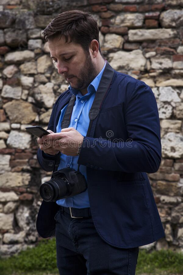 Photographer outdoors. Transfering photos from photocamera to smartphone royalty free stock image