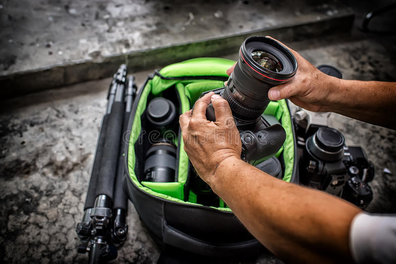Photographer pack his camera and lenses to bagpack. stock image