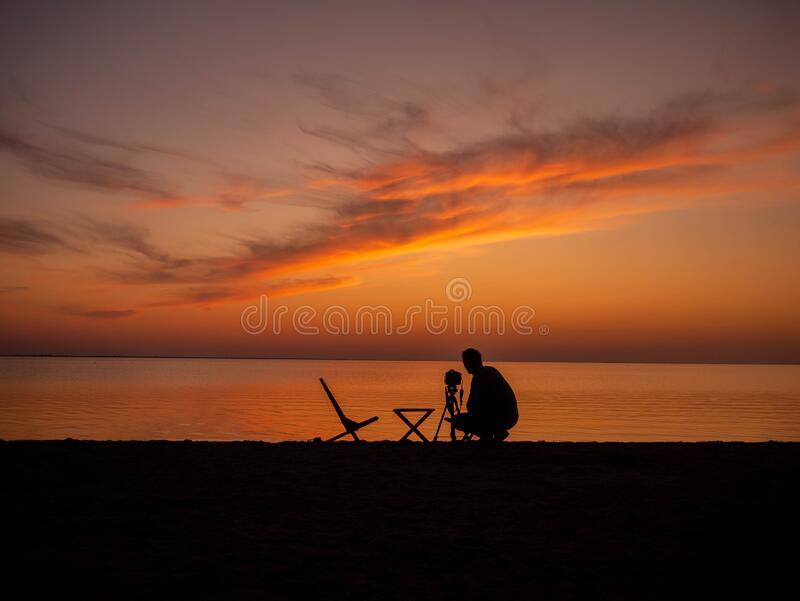 Photographer photographing sunset near sea. Beautiful view at sunset at sea royalty free stock photography