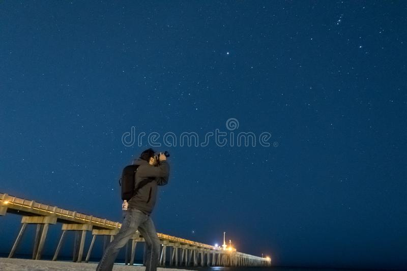 A photographer photographs the night time sky. royalty free stock photography