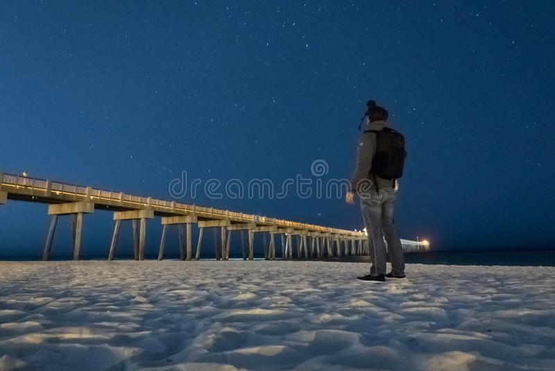 A photographer photographs the night time sky. stock photo