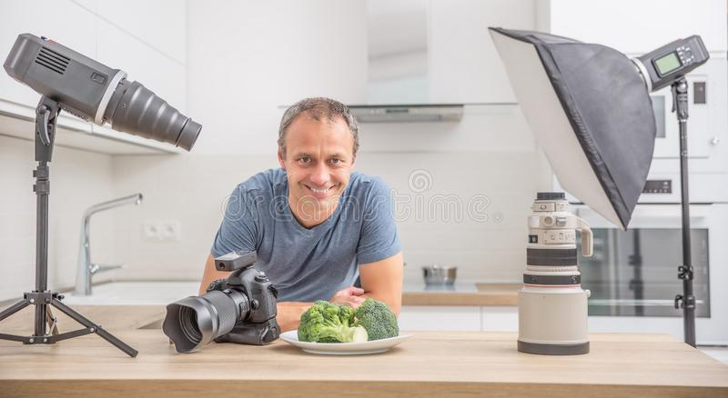 Photographer professional in her studio kitchen with equipment c. Amera flash lights and lenses, food, photography, man, young, taking, creative, working, object royalty free stock images