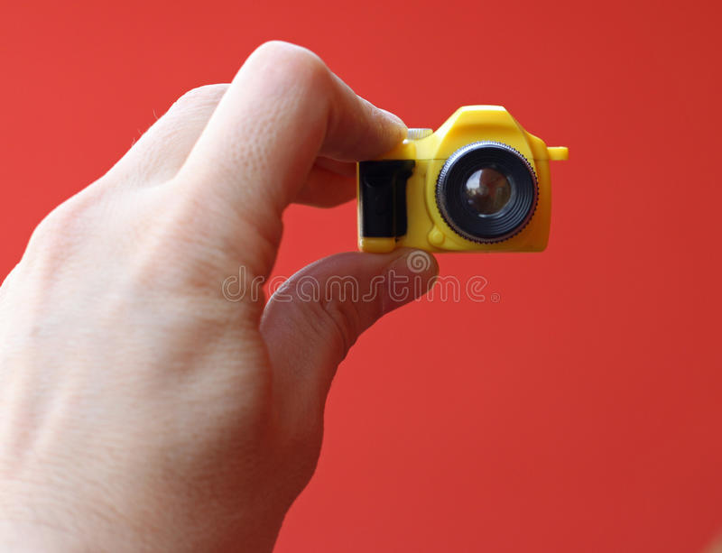 Photographer while on a self-timer. With a small yellow toy camera stock photography