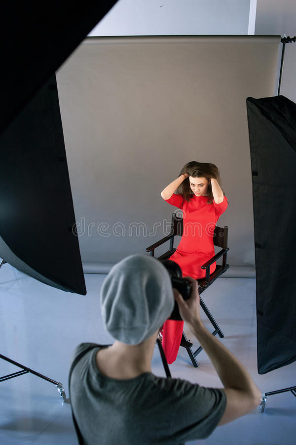 Photographer shoot model in red at studio session stock images