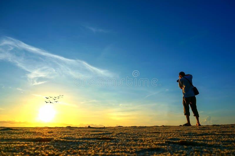 Photographer shooting near the beach when sun rising royalty free stock photos