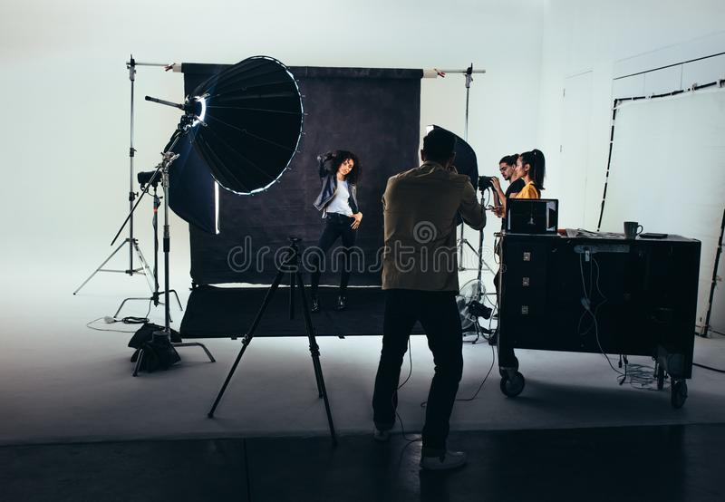 Photographer shooting photos of a female model with studio flash lights on. Photographer with his team during a photo shoot royalty free stock photography