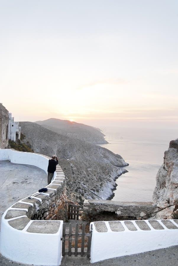Photographer shooting sunset. Photographer shooting a beautiful sunset scenery in Folegandros island, Greece stock photography