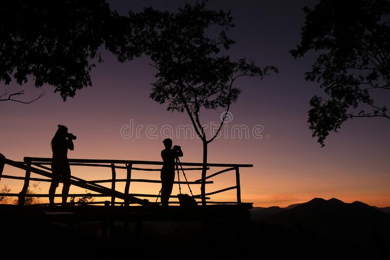 Photographer silhouette on the mountain taking photo shooting landscape with sunset or sunrise - photographer woman with camera. Photographer silhouette on the stock image