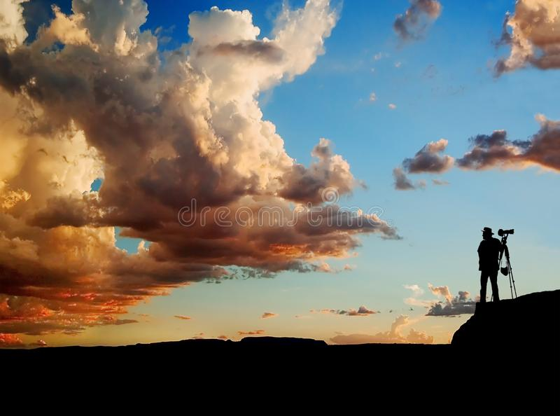 PHOTOGRAPHER SILHOUETTE STANDING AT EDGE OF ROCKS WITH DRAMATIC SUNSET IN BACKGROUND stock photos