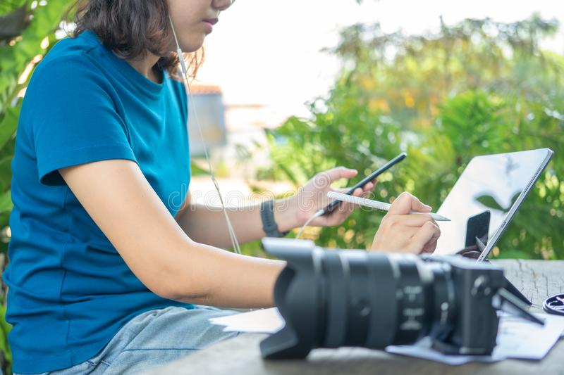 Photographer sitting and editing photos using a tablet. Portable size, smart features In a coffee shop or caf royalty free stock photos