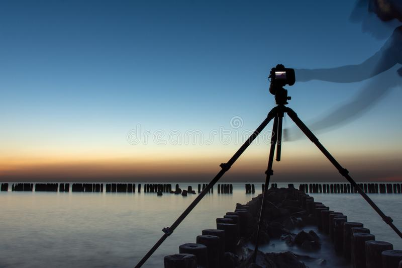Photographer standing on the breakwater by the sea. Camera set on a tripod. sunset stock images