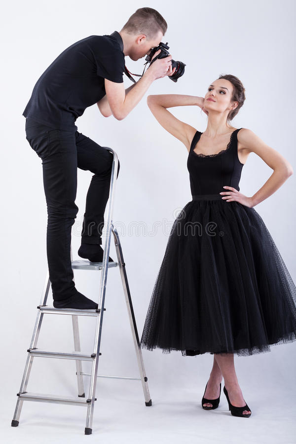 Photographer standing on the ladder and taking a photo royalty free stock image