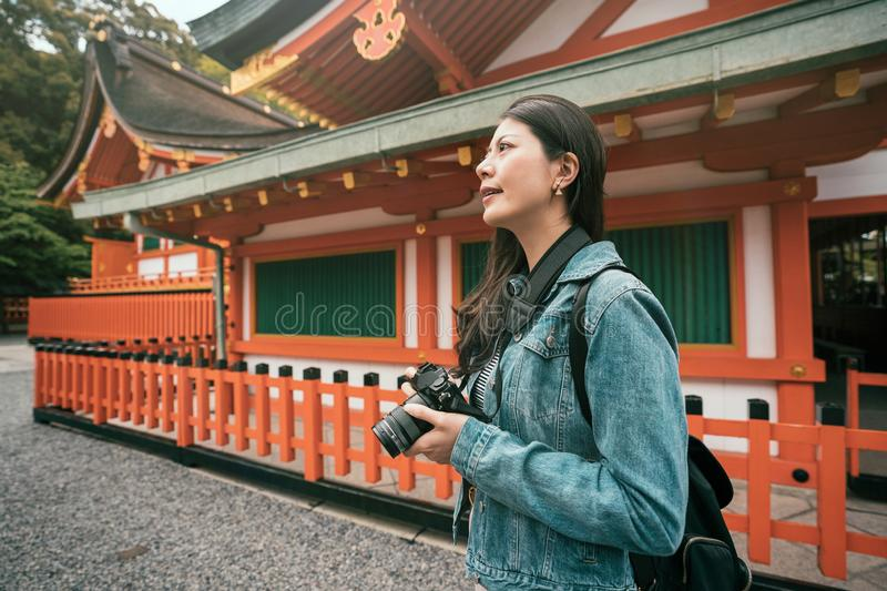 Photographer standing near red wooden temple royalty free stock photos