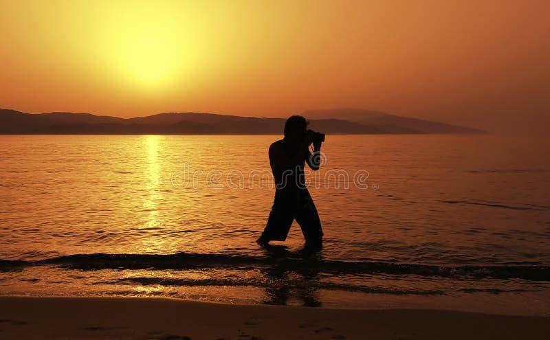Photographer at sunset on the beach stock photo