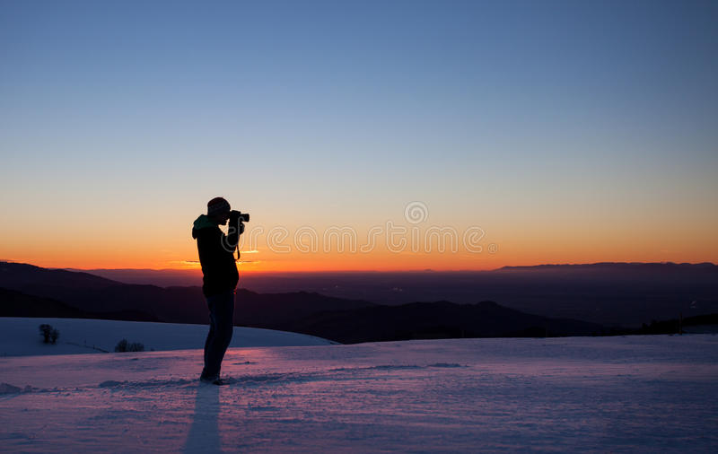 Photographer in sunset in winter landscape. Silhouette of photographer in sunset in winter landscape stock image