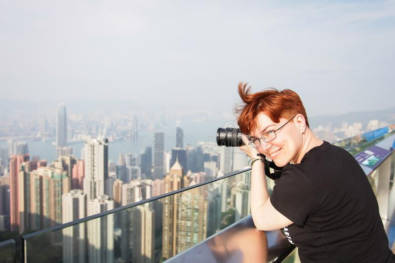 Photographer take photo of city. red-haired woman taking pictures of Hong Kong royalty free stock image