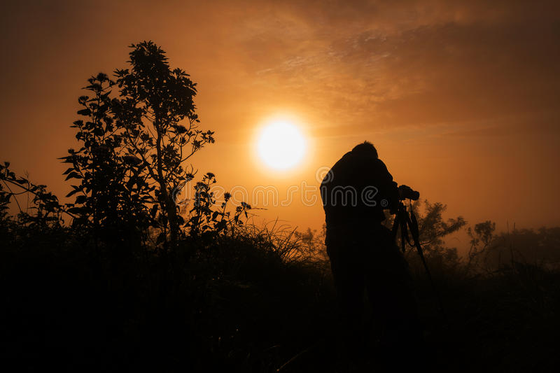 Photographer takes photos the first rays of the rising sun. On Mountain. sunrise in thailand royalty free stock photos