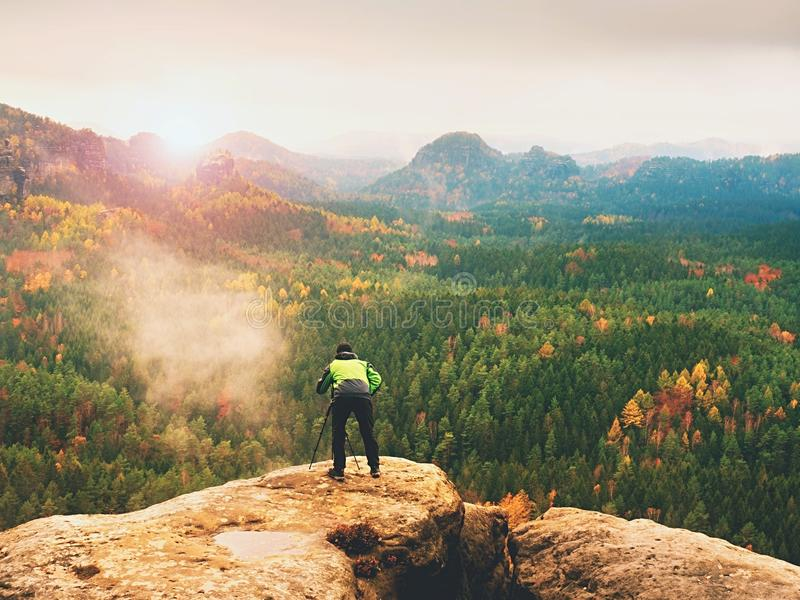 Photographer takes picture of spring nature from sharp rocks. Hiker in green jacket stay with camera on tripod. Hobby photographer takes picture of spring nature royalty free stock photography