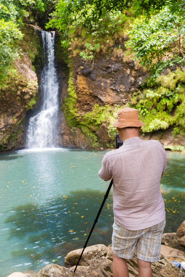 Photographer taking photo of Chamouze waterfall. Mauritius royalty free stock photography