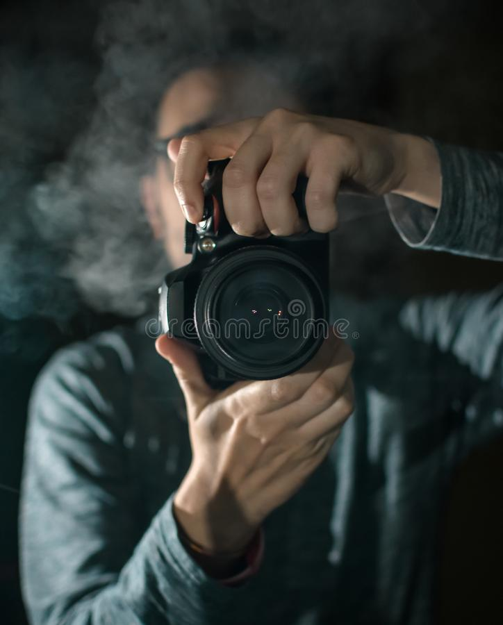 Professional photographer with a camera. Black background royalty free stock photos