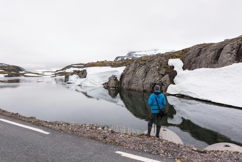 Photographer taking photo of typical norwegian landscape. With snowy mountains and clear lake near the famous Aurlandsvegen mountain road, Aurland, Norway royalty free stock images