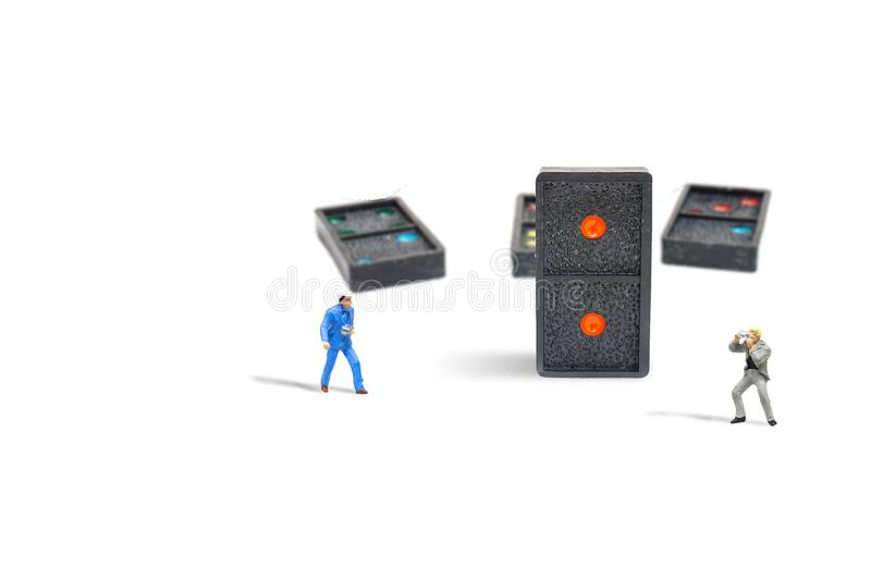 Photographer taking photograph old black dominoes pieces with colorful dot isolated standing on white background. Business Leadership Concept : Miniature stock images