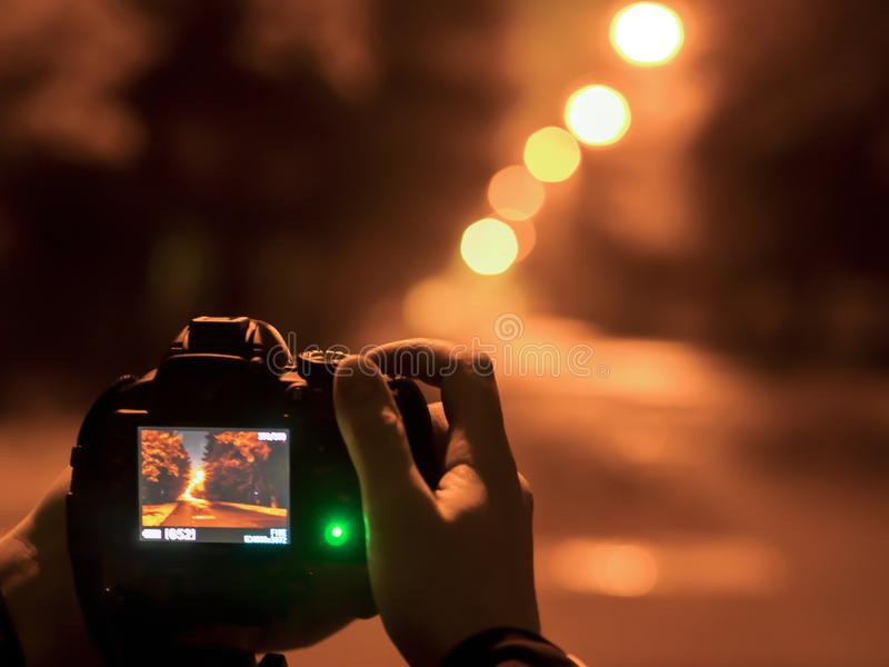 Photographer taking photos with tripot at night. street photography with tripod on the street royalty free stock image