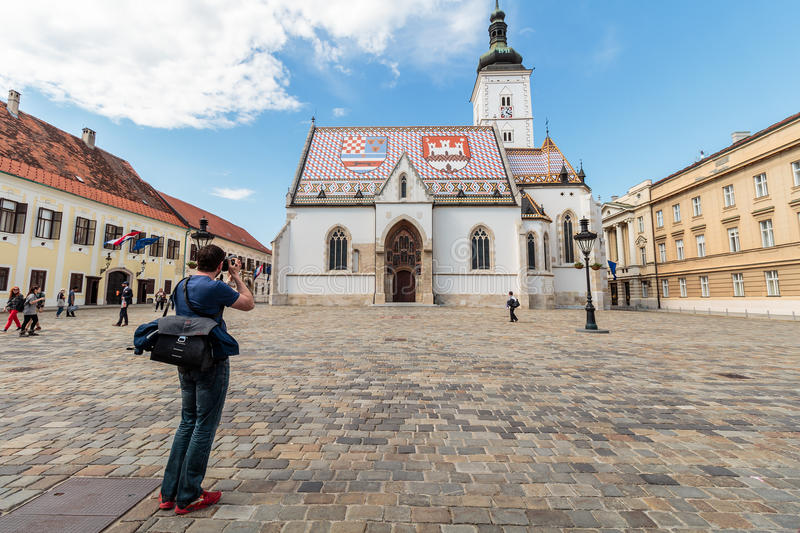 Photographer taking picture of St` Mark`s square. ZAGREB, CROATIA - MAY 07, 2016: Photographer taking picture of St` Mark`s square and the Church of St. Mark royalty free stock images