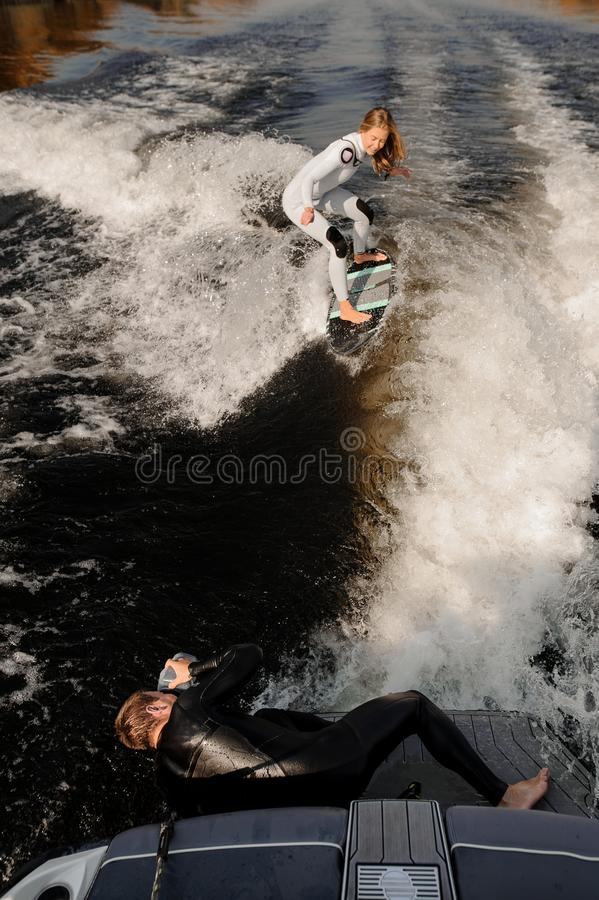 Photographer taking pictures lying on the motorboat of the girl riding on the wake surf. Photographer taking pictures with a camera in waterproof cover lying on royalty free stock photo