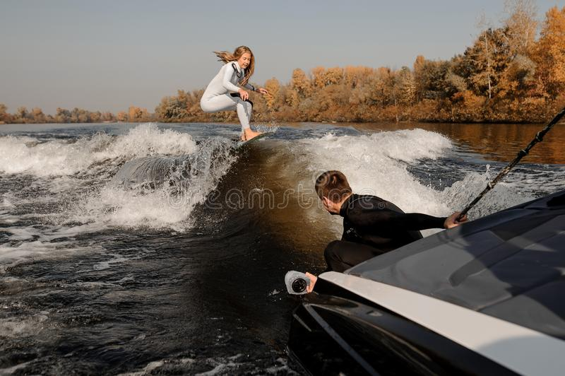 Photographer taking pictures from the motorboat of the girl riding on the wake surf royalty free stock photo
