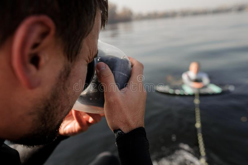 Photographer taking pictures from the motorboat of the girl on the wake surf stock photography