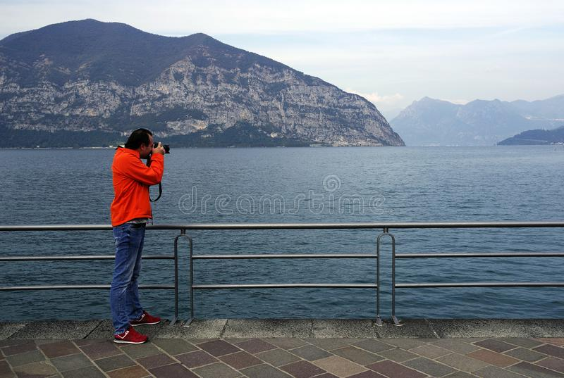 Photographer taking pictures on the shore of Iseo Lake royalty free stock photos