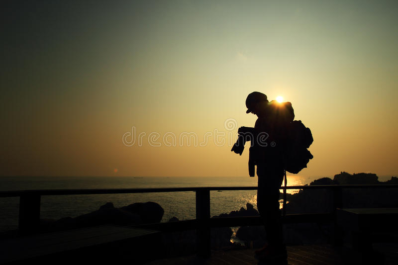 Photographer taking a sunrise picture. Man is taking a picture from the sunrise on the island and review the picture stock photography