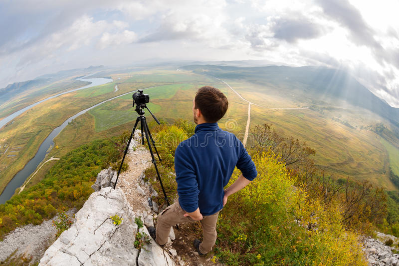 Photographer on top of the mountain takes on the camera stock image