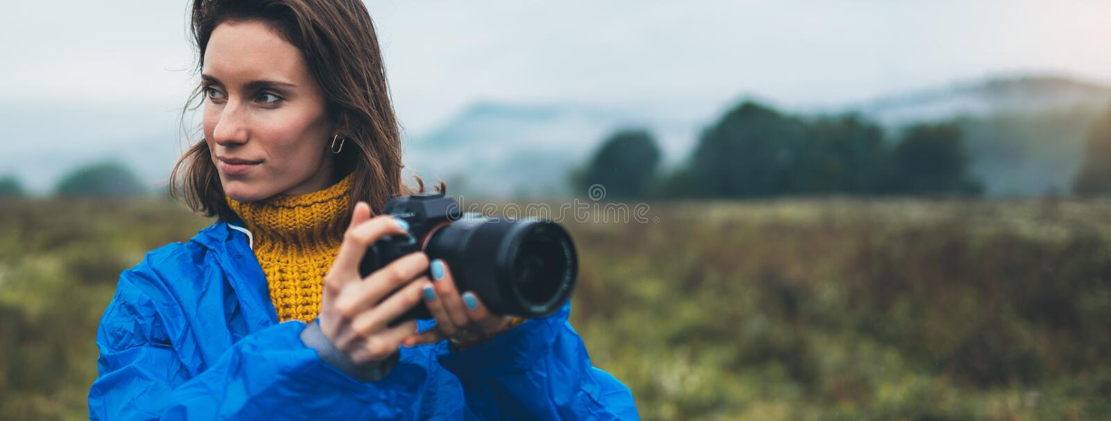 Photographer tourist girl in blue raincoat hold in female hands photo camera take photography froggy mountain, traveler shooting royalty free stock photos