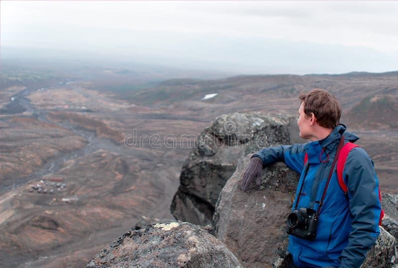 Photographer traveler on top of the mountain, on the edge of the cliff photographs. Fog, mountain peak stock photo