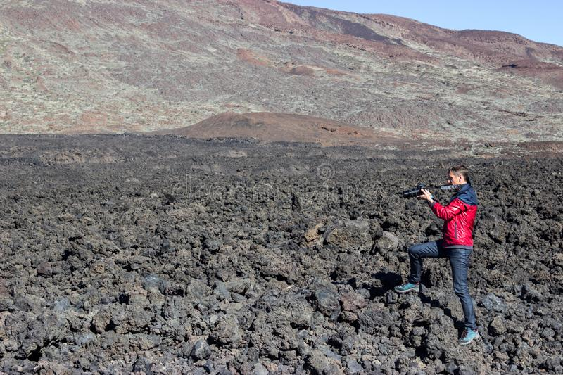 Photographer and traveller taking a picture of volcanic lava stones standing on clinker field near mountains. Photographer and traveller taking a picture of stock photos