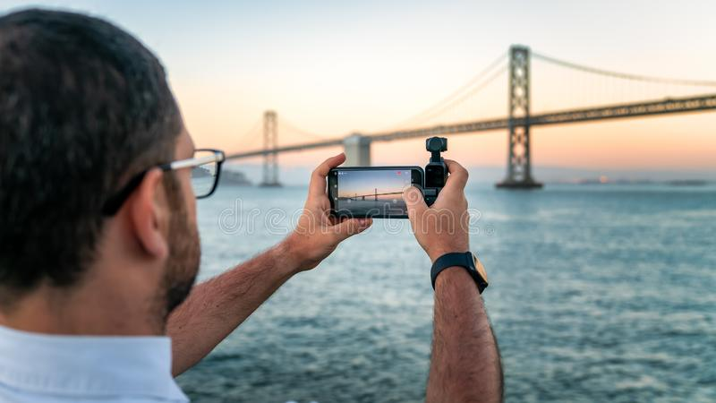 A photographer is using DJI Osmo Pocket to take footage of a Bay Bridge, San Francisco, USA stock photos
