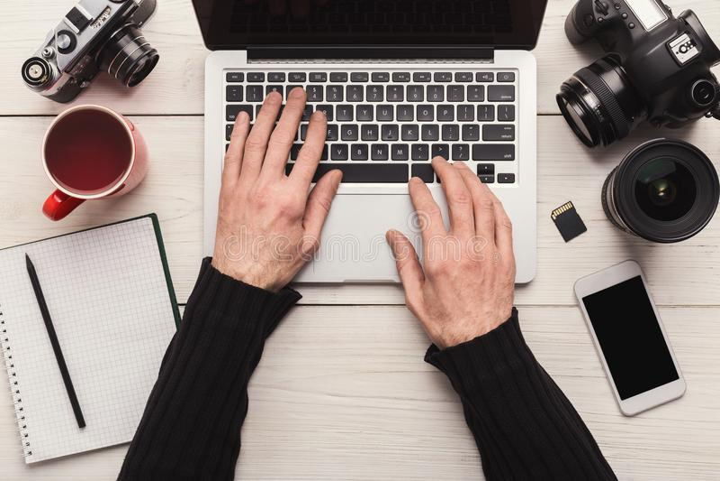 Photographer using laptop on workplace stock photo