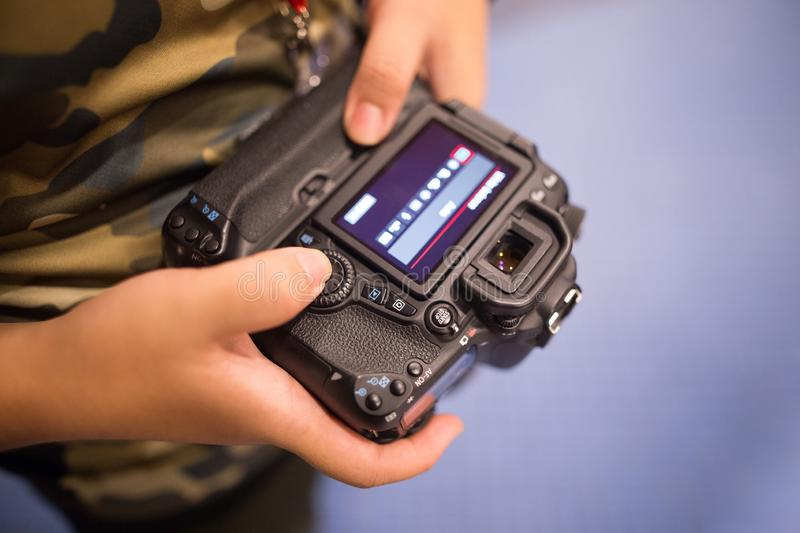 Photographer viewing the LCD display and changing settings via wheel controls on DSLR camera.  stock photography